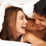 Happy Couple in Bed --- Image by © Cesár Vera/Corbis